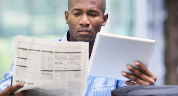 Man looking at different sources