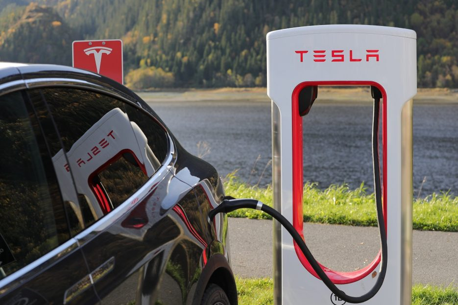 Green cars, like this charging Tesla, is the focus of a 5 paragraph argumentative essay